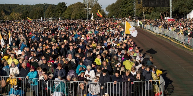 Faithful gather to follow Pope Francis' celebrating Holy Mass at the Confluence Park in Kaunas, Lithuania, Sunday, Sept. 23, 2018.