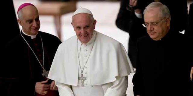 Pope Francis is flanked by Monsignor Vincenzo Paglia and Father Leonardo Sapienza at the end of an audience with workers of the Catholic Shrines in the Paul VI Hall at the Vatican, Thursday, Jan. 21, 2016. (AP Photo/Alessandra Tarantino)