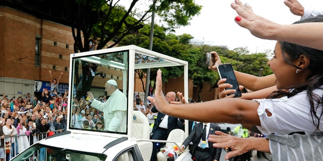 People wave to Pope Francis in the popemobile in Medellin, Colombia, Saturday, Sept. 9, 2017.