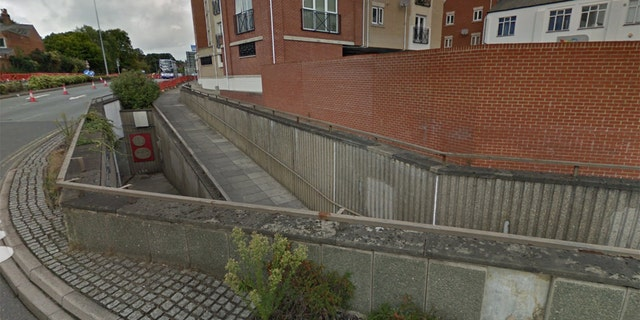 A view of the wall before the accident shows the walkway passing below it.