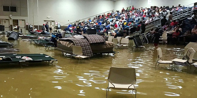 In this photo provided by Beulah Johnson, evacuees sit in the bleachers at the Bowers Civic Center in Port Arthur, Texas, Wednesday, Aug. 30, 2017, after floodwaters caused by Tropical Storm Harvey inundated the facility overnight