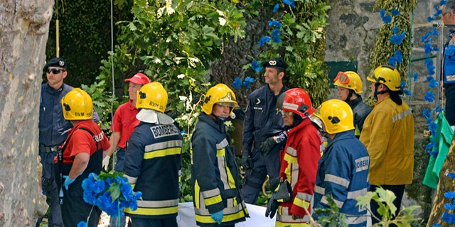 Firefighters hold a blanket as bodies are removed from the scene where a tree fell on a large crowd in Portugal.
