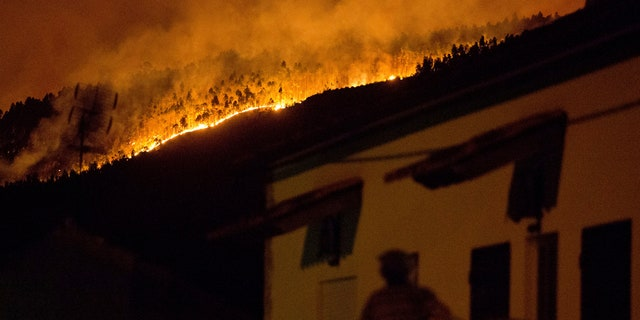 A man on the balcony of a house looks up at a forest fire raging on a hillside above the village of Avelar, central Portugal, before sunrise Sunday, June 18, 2017.