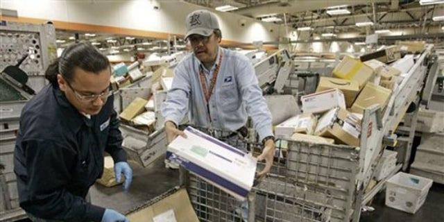FILE: U.S. Postal Service mail handlers sort packages at the USPS San Francisco center.