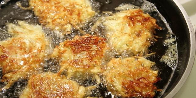 Potato latkes for Hanukah frying in oil.