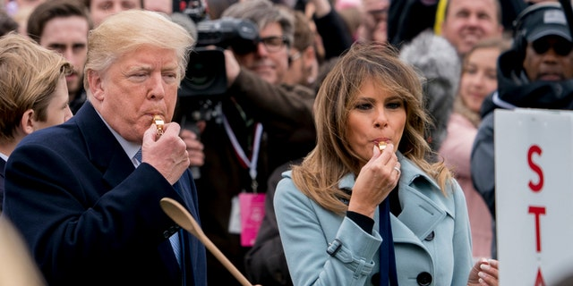 President Donald Trump and first lady Melania Trump blow whistles to start a race at the annual White House Easter Egg Roll on the South Lawn of the White House in Washington, Monday, April 2, 2018. (AP Photo/Andrew Harnik)