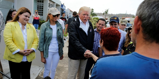 President Trump greeting people while walking through the hurricane-affected areas of a neighborhood in San Juan with first lady Melania Trump on October 3, 2017.