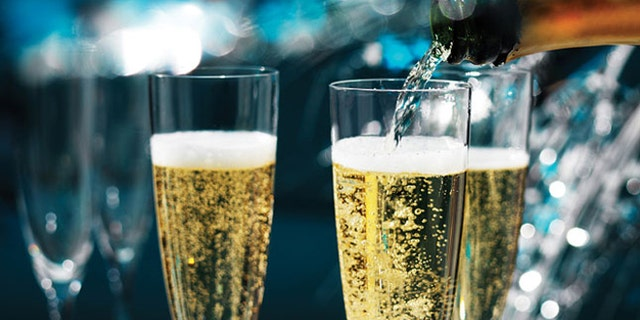 Champagne being poured into champagne flutes, in a very sparkly, festive party.