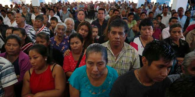 This Sept. 21, 2016 photo shows a packed Our Lady of Asuncion Church for the funeral Mass of slain Rev. Jose Alfredo Suarez de la Cruz, who was found bound and shot to death alongside another priest, in Paso Blanco, Veracruz state, Mexico, his hometown. The killings in the troubled Gulf state of Veracruz came at a moment of heightened tension between the Roman Catholic Church and Mexicoââ¬â¢s government. (AP Photo/Marco Ugarte)