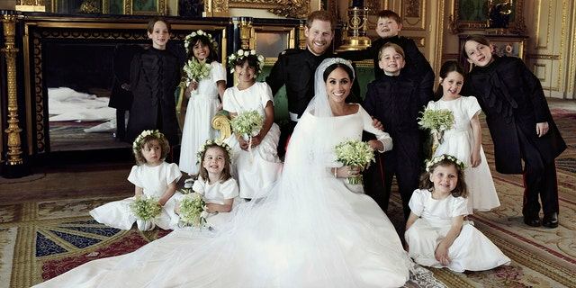 Prince Harry and Meghan Markle, center, in Windsor Castle, Windsor, England, Saturday May 19, 2018. Others in photo from left, back row, Brian Mulroney, Remi Litt, Rylan Litt, Jasper Dyer, Prince George, Ivy Mulroney, John Mulroney; front row, Zalie Warren, Princess Charlotte, Florence van Cutsem.