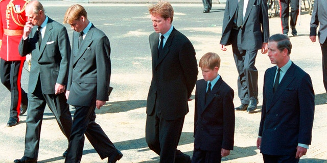 FILE - In this Saturday Sept. 6, 1997 file photo, from left Prince Philip, Prince William, Earl Spencer, Prince Harry and Prince Charles follow the coffin of Diana, Princess of Wales along Horse Guards Parade toward Westminster Abbey, London. Long dismissed as a party boy, Prince Harry has transformed himself in the public eye and enjoys widespread popularity as he prepares to marry Meghan Markle on May 19, 2018. Harry has become a forceful advocate for veterans and won admiration by speaking openly about his struggle with the pain caused by the early death of his mother, Princess Diana. (AP Photo/David Brauchli, file)