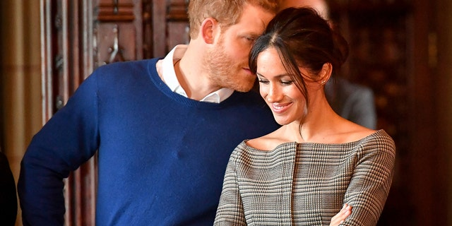 Prince Harry whispers to Meghan Markle as they watch a performance by a Welsh choir in the banqueting hall during a visit to Cardiff Castle in Cardiff, Britain, January 18, 2018.