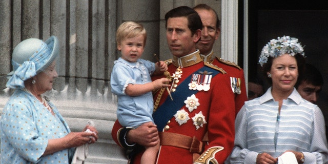 A young Prince William clings tight to his father, Prince William, during the Trooping the Colour festivities in 1984.