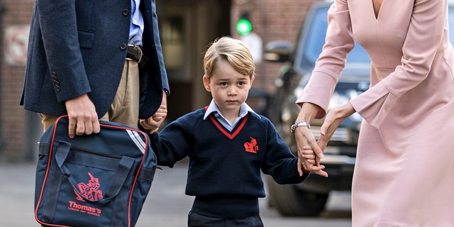 Britain's Prince William accompanies Prince George as he is met by Helen Haslem - the head of the lower school on arrival for his first day of school at Thomas's school in Battersea, London, Thursday, Sept. 7, 2017.  Prince William's pregnant wife Kate was too ill with morning sickness Thursday to take young Prince George to his first day of school.  (Richard Pohle/Pool Photo via AP)