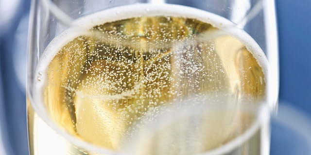 Close up of champagne bubbling in a champagne flute.
