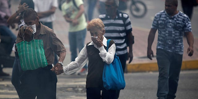 People walk in a cloud of tear gas during a rally against Venezuela's President Nicolas Maduro's government in Caracas, Venezuela April 10, 2017.