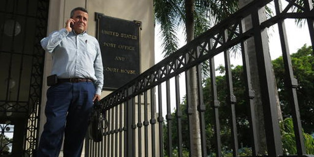 Attorney Santiago Mari talks to a client in front of a federal courthouse in San Juan, Puerto Rico.