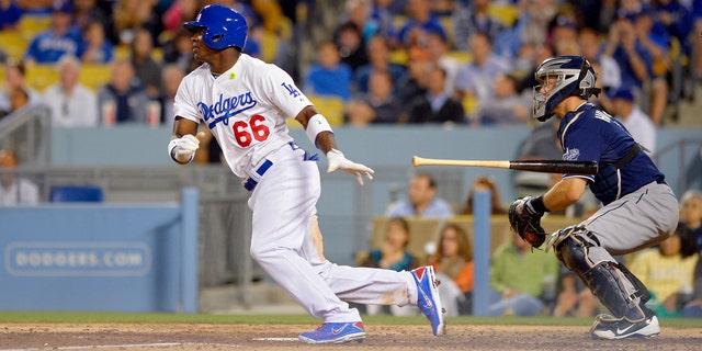 El jugador de los Dodgers de Los Angeles, Yasiel Puig, conecta un sencillo contra los Padres de San Diego en su primer partido en Grandes Ligas el lunes, 3 de junio de 2013, en Los Angeles. (AP Photo/Mark J. Terrill)