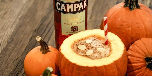 Pumpkin Spice Negroni served in a pumpkin bowl.
