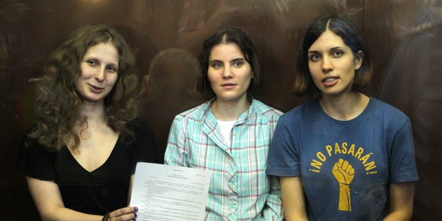 Aug 17, 2012: Feminist punk group Pussy Riot members, from left, Maria Alekhina, Yekaterina Samutsevich, and Nadezhda Tolokonnikova show the court's verdict as they sit in a glass cage at a court room in Moscow, Russia.