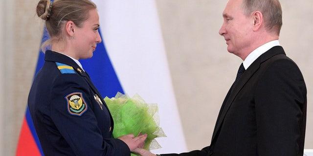 Putin presents flowers to Sgt. Tatyana Kovaleva in the Kremlin on Thursday.