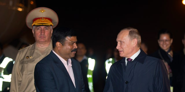 Dec. 10, 2014: Russian President Vladimir Putin, right, is received by Indian Minister of State for Petroleum, Dharmendra Pradhan