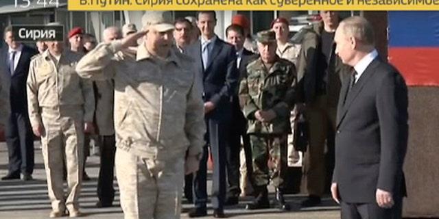 Sergei Surovikin, Russian Commander in Syria, 3rd left, reports to President Vladimir Putin, right, as Syrian President Bashar Assad, 4th left, listens, at the Hemeimeem air base in Syria.
