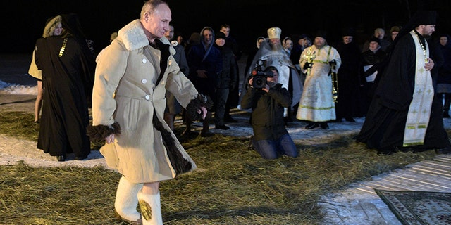 Putin wore a sheepskin coat and felt boots before stripping down to his bathing trucks.