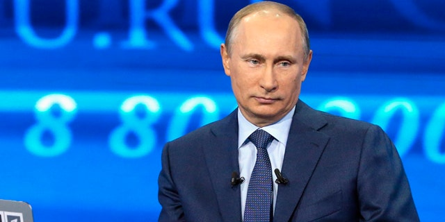 """April 25, 2013: Russian President Vladimir Putin listens to a question during an annual call-in show on Russian television """"Conversation With Vladimir Putin""""  in Moscow."""