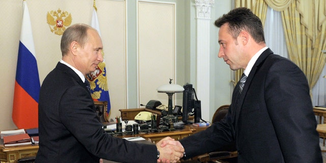 May 18, 2012: Russian President Vladimir Putin shakes hands with Igor Kholmanskikh, right, a section head at the Uralvagonzavod tank factory in the Urals city of Nizhny Tagil that builds battle tanks, in Novo-Ogaryovo residence outside Moscow.