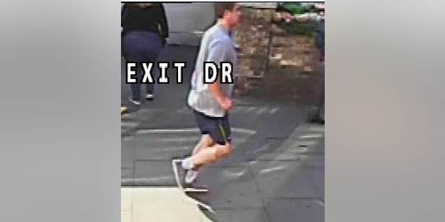 CCTV image of the man London police say pushed an unidentified woman in front of an incoming bus that narrowly missed her.