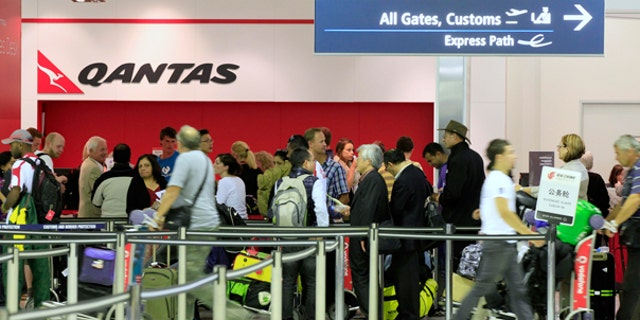 Oct. 29: Travelers gather at the Qantas sales desk at Sydney Airport in Sydney.