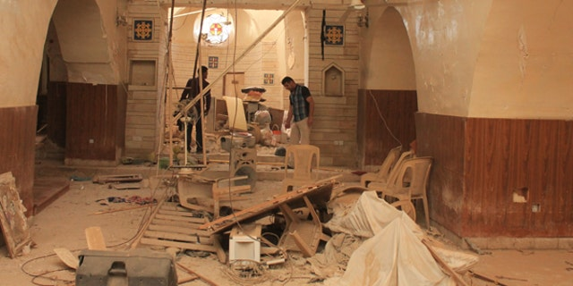 Relief workers survey the damage to a church in Qaraqosh.
