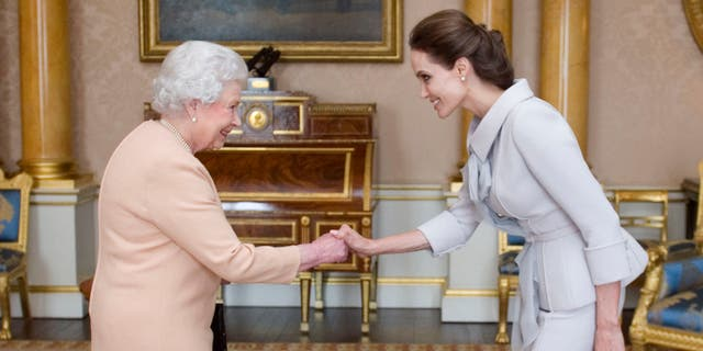 October 10, 2014. Angelina Jolie, right, is presented with the Insignia of an Honorary Dame Grand Cross of the Most Distinguished Order of St Michael and St George by Queen Elizabeth II at Buckingham Palace, London.