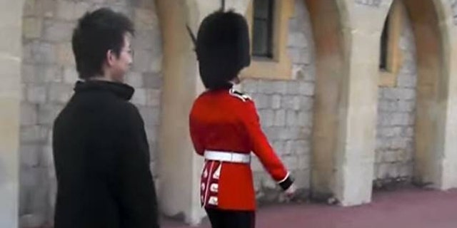 The tourist was mocking the soldier by walking alongside of him.