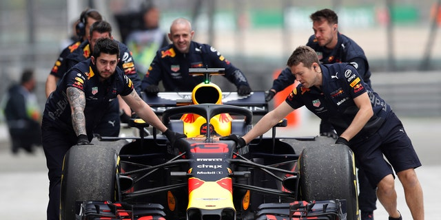 The car of Red Bull driver Daniel Ricciardo of Australia is pushed back to his team's garage after an engine trouble during the third practice session for the Chinese Formula One Grand Prix at the Shanghai International Circuit in Shanghai, Saturday, April 14, 2018.
