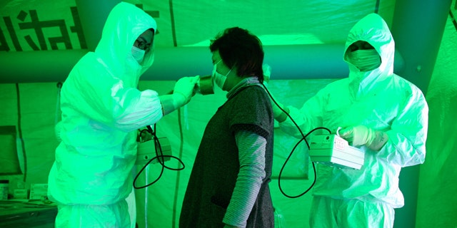 Medical staff use a Geiger counter to screen a woman for possible radiation exposure at a public welfare centre in Hitachi City, Ibaraki, March 16, 2011, after she evacuated from an area within 20km (12.4 miles) radius of the Fukushima Daiichi nuclear plant. The woman was tested negative for radiation exposure. Radiation has been released into the atmosphere at the Fukushima Daiichi nuclear plant run by Tokyo Electric Power Co. on the country's northeast coast, which was badly damaged after a massive earthquake and tsunami on March 11.