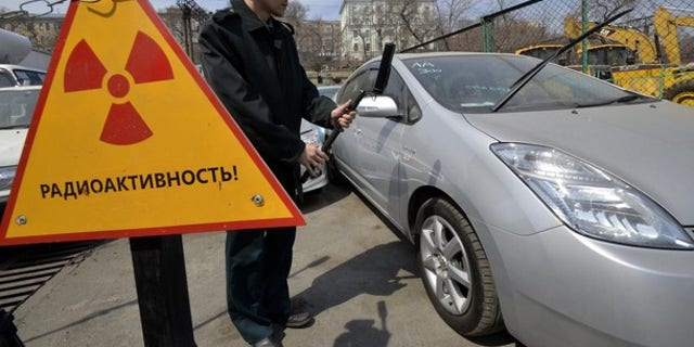 A customs officer measures the radiation level of an automobile delivered from Japan, in Russia's far eastern city of Vladivostok April 14, 2011.