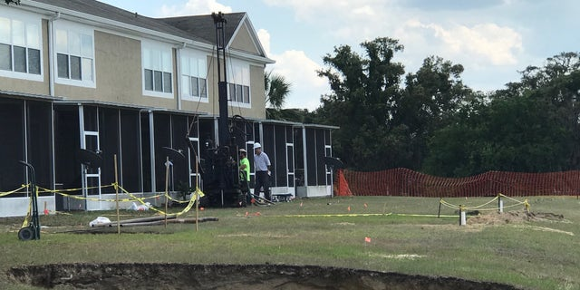 Crews continue drilling for soil samples and running ground-penetrating radar around the retention pond where multiple sinkholes opened.