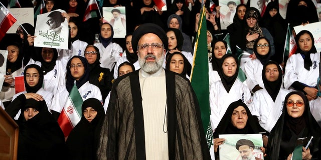 In this April 29, 2017 file photo, Iranian cleric and presidential candidate Ebrahim Raisi, center, stands among his supporters, during a campaign rally in Tehran, Iran.