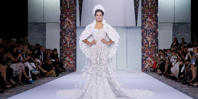 A model presents a wedding gown from Ralph & Russo at a fashion show in 2016. British media outlets speculate that the design house was chosen to make Markle's dress, as well.