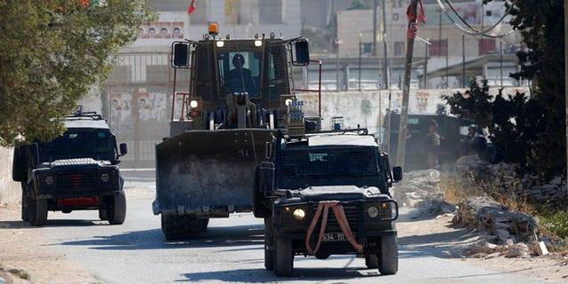 Israeli security forces raid the West Bank village of Deir Abu Mash'al near Ramallah, Saturday.