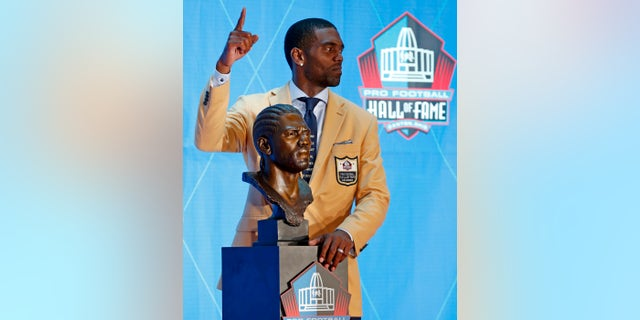 Former NFL wide receiver Randy Moss poses with a bust of himself during inductions at the Pro Football Hall of Fame, Saturday, Aug. 4, 2018 in Canton, Ohio.
