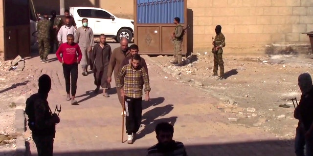 ISIS fighters who surrendered enter a base of the U.S.-backed Syrian Democratic Forces in Raqqa.