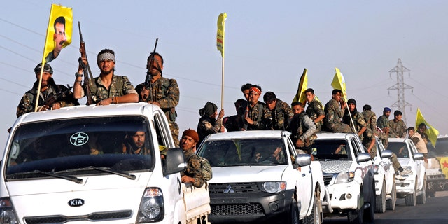 Fighters of Syrian Democratic Forces ride on trucks as their convoy passes in Ain Issa.