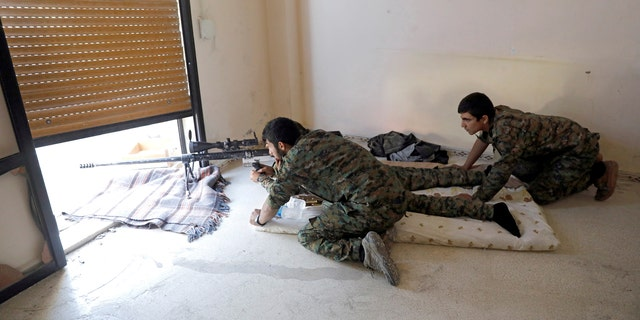 Fighters of Syrian Democratic Forces take up position inside a building opposite the National Hospital where ISIS fighters were holed up.