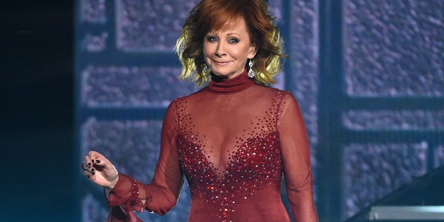McEntire reportedly wore seven dresses when she hosted the ACM Awards in 2018 after a hiatus. She also donned a pair of slippers with this iconic red gown — which she first wore in 1993. (Photo by Chris Pizzello/Invision/AP)