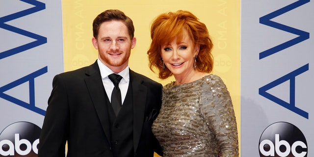 Race driver Shelby Blackstock and singer Reba McEntire arrive at the 50th Annual Country Music Association Awards in Nashville, Tennessee, U.S., November 2, 2016. REUTERS/Jamie Gilliam - RTX2RMKA