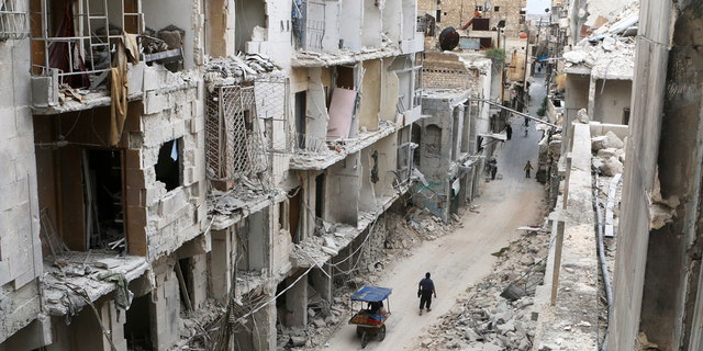 Residents walk near damaged buildings in the rebel held area of Old Aleppo, Syria May 5, 2016. REUTERS/Abdalrhman Ismail/File Photo - RC1FE5D0C050