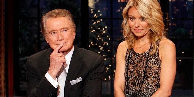 "Television host Regis Philbin says goodbye with co-host Kelly Ripa (R) during his final show of on ""Live With Regis and Kelly"" in New York, November 18, 2011."